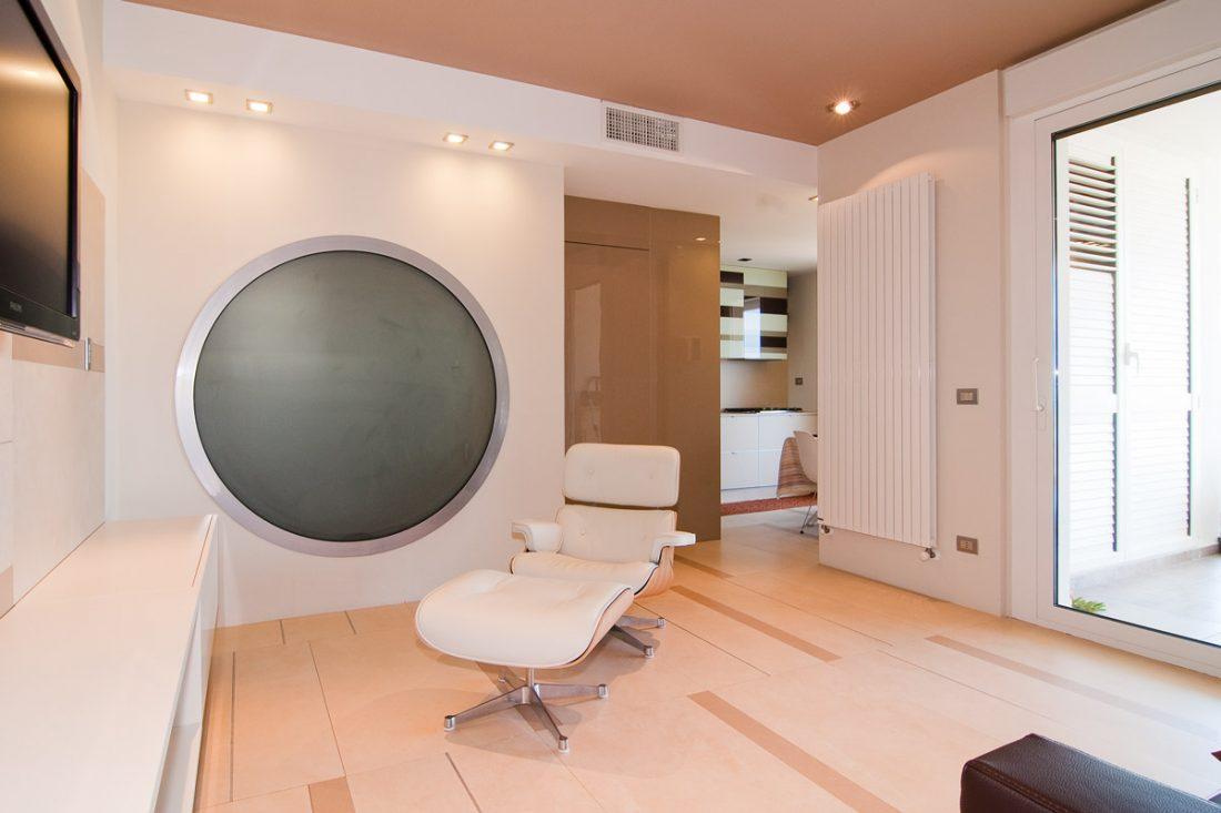 Immagine di un progetto di interior design a Vasto. Si possono vedere il salotto moderno con eames chair, un'ampia vetrata e un grande oblò circolare