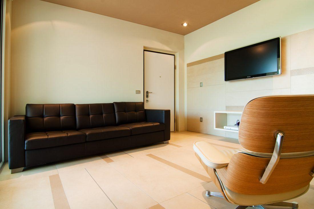 Immagine di un progetto di interior design con dettaglio del salotto con un divano in pelle e una eames chair