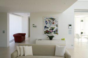 Salotto moderno completamente bianco, divano in pelle rossa, dipinto moderno e tavolo tulip saarinen bianco