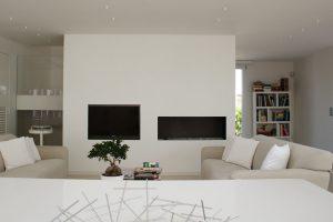 Un salotto moderno bianco con un elegante bonsai appoggiato sul tavolo tra i due divani in tessuto bianco