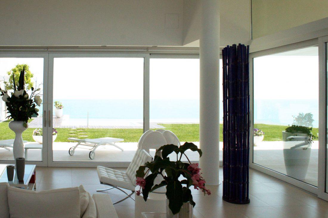 Immagine di un ampio salotto con vetrate ampie e affacciate alla piscina
