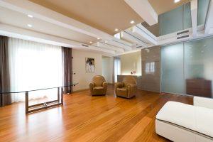 Uno spazioso soggiorno con parquet di legno, poltrone di pelle e tavolo con piano in vetro affacciato ad un'ampia vetrata