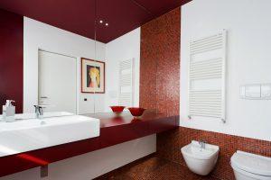 Un bagno moderno a tinte rosse decorato con un botero