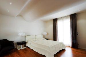 Una camera da letto matrimoniale bianca con il soffitto curvilineo che ricorda un'onda