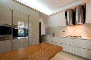 Una cucina moderna con colonne color tortora e un tavolo con piano in legno