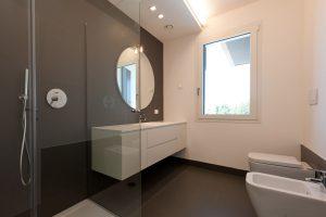 Rinnovo di un bagno con arredo moderno e specchio circolare