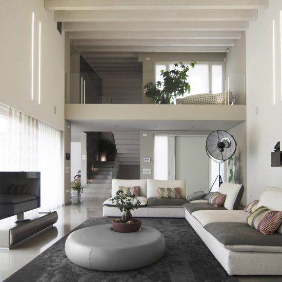 Salotto a doppia altezza con divano bianco e grigio, una lampada di design e un bonsai a decorare il coffee table