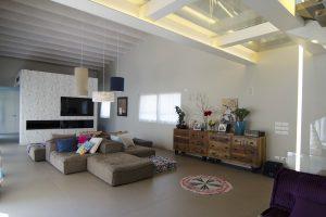 Interior design di un ampio soggiorno a doppia altezza con divano isola in tessuto grigio
