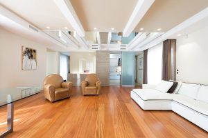 Spazioso soggiorno con parquet, poltrone di pelle marrone chiaro e divano bianco